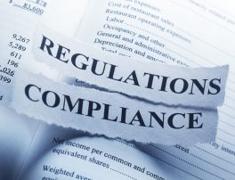 The words Regulation and Compliance are  printed on a torn pieces of paper that sit on a corporate financial document. The image illustrates the concept of government oversight and corporate and financial governance.